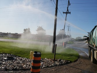view of a truck spraying water on grass